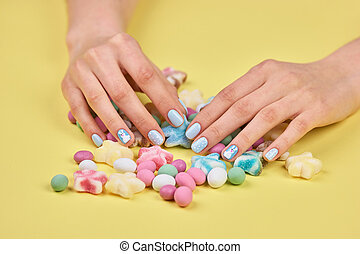 Colorful candies and woman hands.
