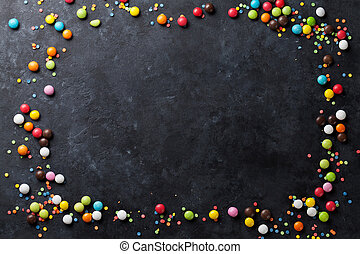 Colorful candies frame on stone background