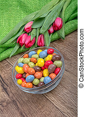 Colorful candies in a glass bowl with tulips on a wooden background