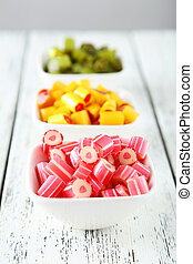 Colorful candies in bowl on white wooden background
