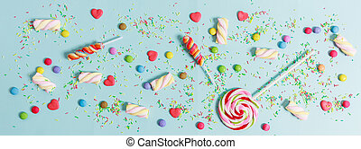 Colorful candies on blue background, top view