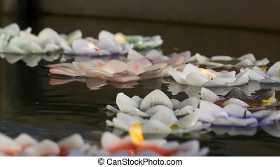Colorful Candles in Lotus Shape Floating on Water in a Buddhist Temple. Pattaya. Thailand.