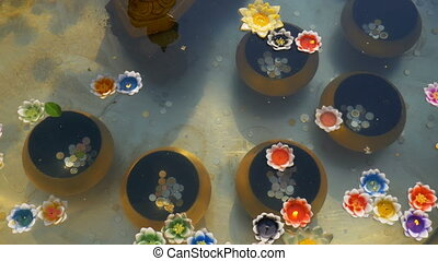 Colorful Candles in Lotus Shape Floating on Water in a...