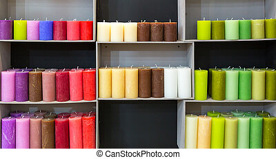 Colorful candles on shelf in decoration shop. Many...