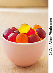 Colorful candy in a bowl on wooden background