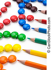 Colorful candys and penciles over white background.