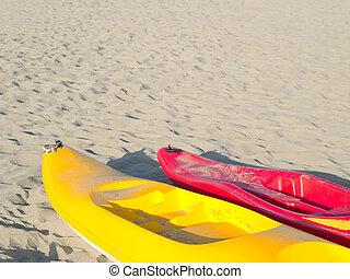 colorful canoes on a light sandy beach
