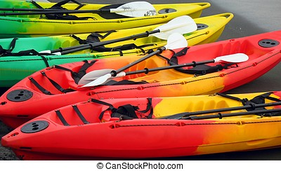 Colorful Canoes - -- resting on a beach with dark grey sand...
