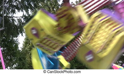 A colorful carnival ride whips around in circles provoking pleasurable moments for its riders.