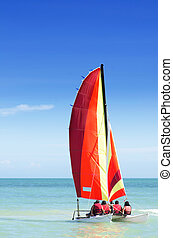 Colorful catamaran with four passengers on board heading out to the sea