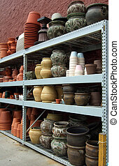 Colorful ceramic gardening pots and vessels sitting on a ...
