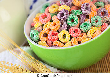 Colorful cereal loops with different fruit flavour in green bowl with milk in the back (Selective Focus, Focus one third into the bowl)