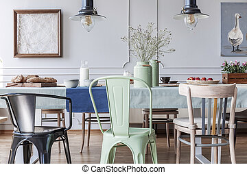 Colorful chairs at table in cottage grey dining room interior with lamps and posters. Real photo