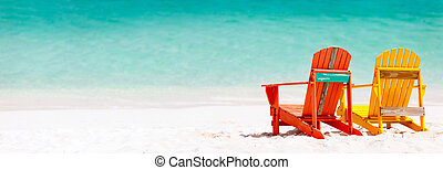 Two colorful wooden chairs at tropical white sand beach in Caribbean, panorama with copy space perfect for banners