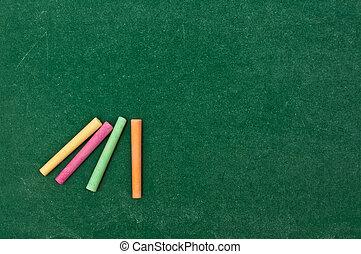Colorful chalk on green chalkboard