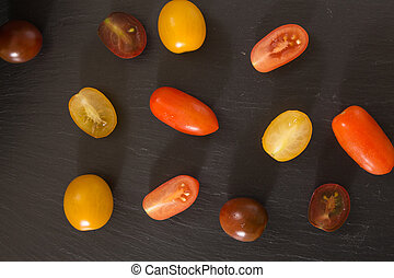 Colorful cherry tomatoes, on black background.