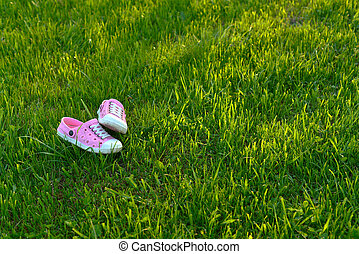Colorful children sandals on playground artificial grass