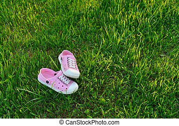 Colorful children sandals on playground grass photo