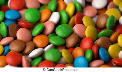 Colorful chocolate candy rotate background.