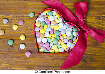 Colorful chocolate pills in a heart shaped box