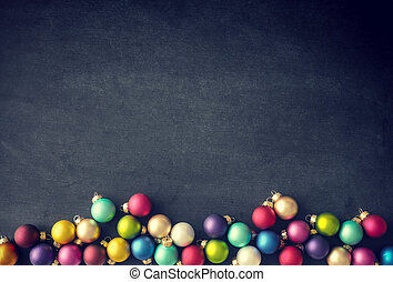 Colorful Christmas baubles on a chalkboard