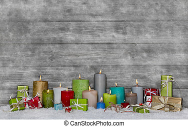 Colorful christmas decoration with different candles on grey and