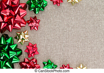 Colorful Christmas foil bow background on burlap