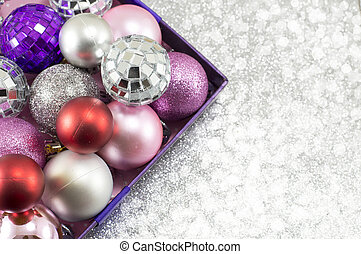 Colorful Christmas ornaments in a bowl against shiny background