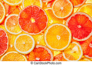Colorful citrus fruit - lemon, orange, grapefruit - slices background. Backlit