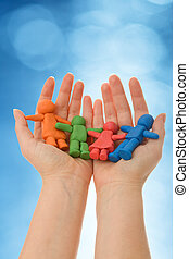 Colorful clay people in woman palm