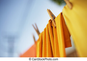 Colorful clothes drying on clothesline. Shallow DOF.
