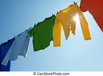 Colorful clothes on a laundry line and sun shining -...