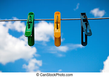 colorful clothespins on a background of blue sky and white clouds