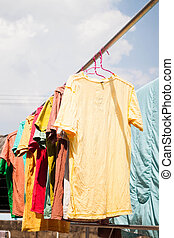 Colorful clothing drying on clothesline under sunlight