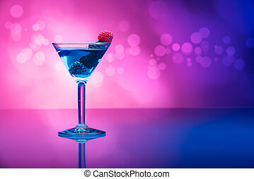 Colorful cocktails garnished with berries, background with light effects