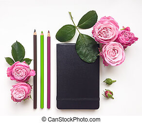 Colorful composition with sketchbook, roses and pencils. Flat lay on white table, top view