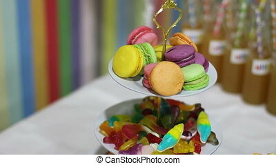 Colorful cookies macarons and chewing sweets on table