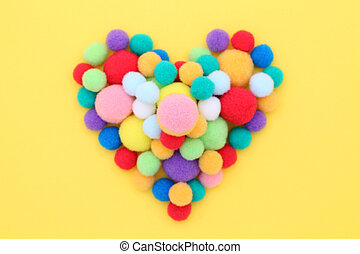 Colorful cotton balls on yellow background