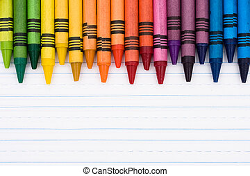 Colorful crayons on a sheet of lined paper, Education background