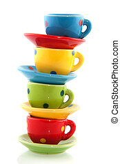 colorful spotted stacked cups and saucers with white background