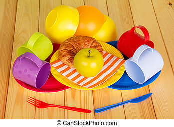 Colorful crockery, croissant and an apple on  background of light wood