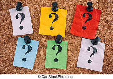 Colorful crumpled paper notes with question marks on a cork board