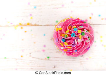 Colorful cup cake on wooden background.
