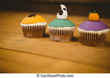 Colorful cup cakes on table during Halloween - Close up of ...