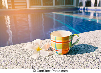 Colorful cup of coffee on the edge of pool