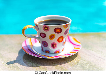 Colorful cup of coffee on the pool