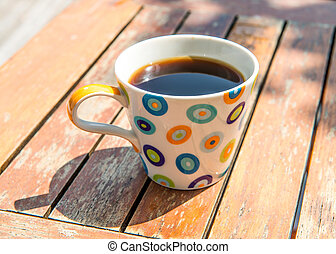 Colorful cup of coffee on wooden table