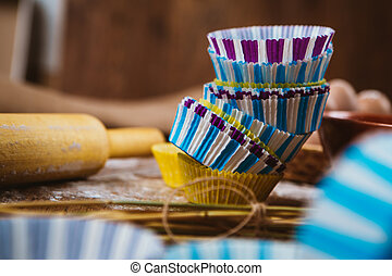 Colorful cupcake wrappers with baking pan on wooden background