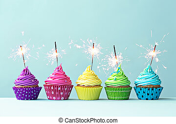 Colorful cupcakes with sparklers - Row of colorful cupcakes...