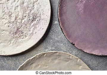 Colorful decorated porcelain plates on a gray marble table....